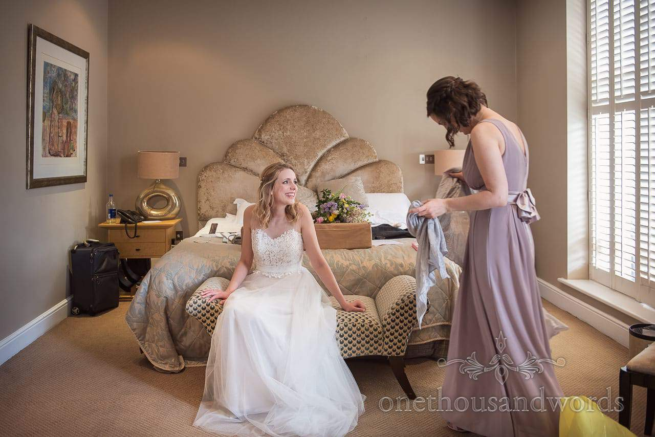 Bride relaxes on wedding morning on Bed at Kings Arms Hotel Dorset with Bridesmaid in Pastel Dress
