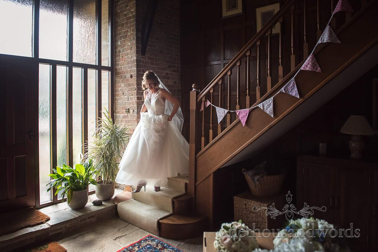 Bride descends wooden staircase with bunting on wedding morning