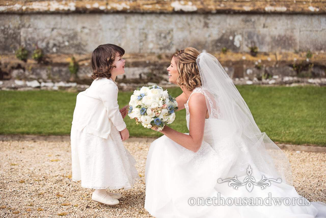 Bride and flower girl laughing at each other at Athelhampton House