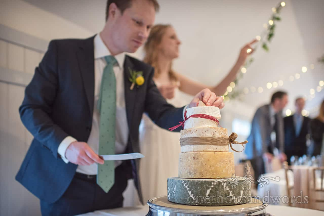 Bride and Groom Cut Four Tier Wedding Cake Made from Cheese with knife