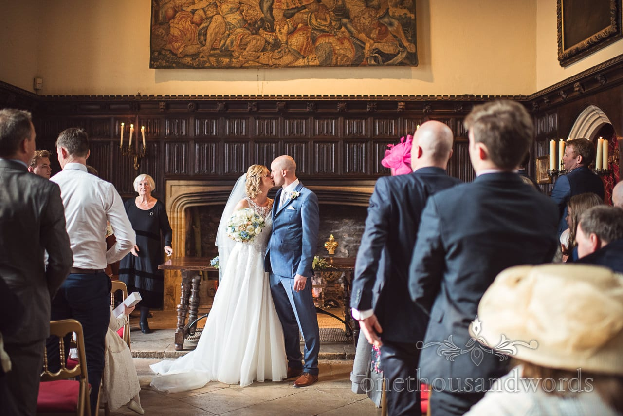 Bride and groom first kiss at Athelhampton House wedding ceremony
