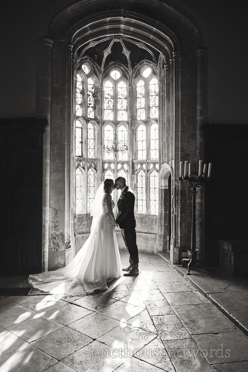Bride and groom kiss in Oriel window at Athelhampton House Wedding