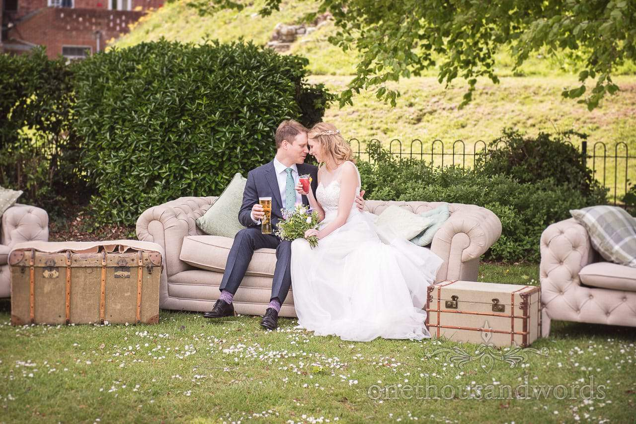 Bride and Groom Kiss on Outdoor Sofa with retro cases at Christchurch Pavilion Park Wedding in Dorset