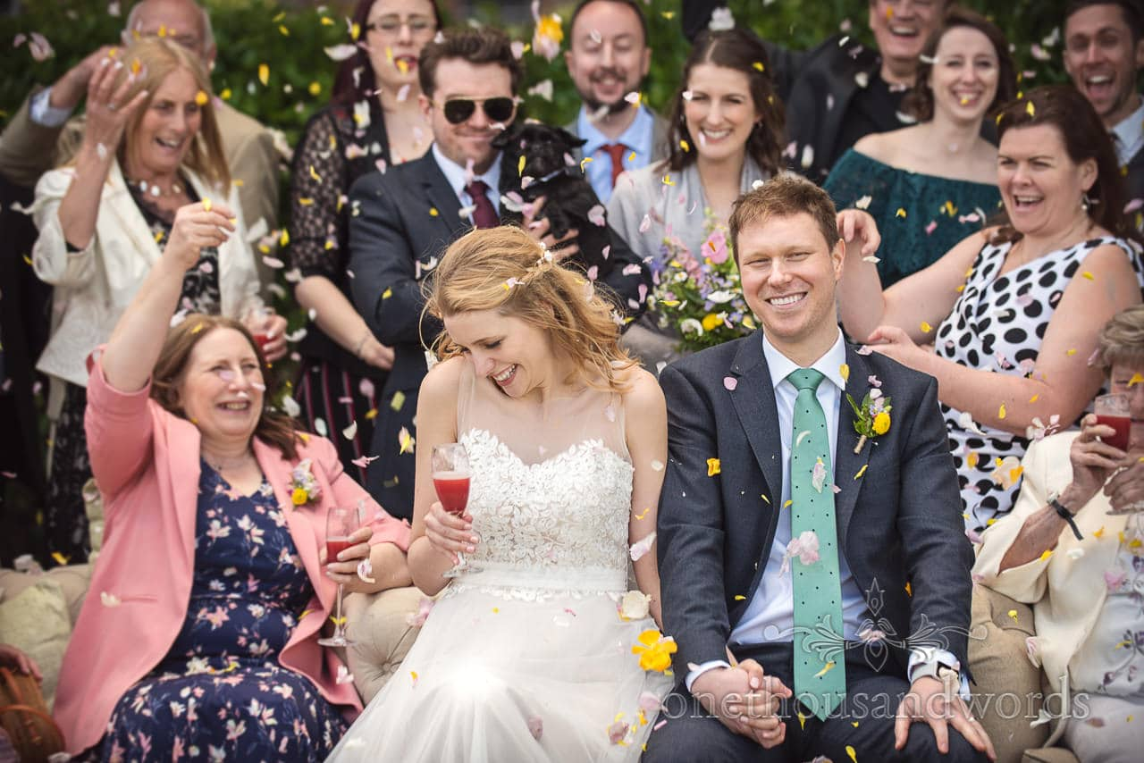Wedding photograph of laughing Bride Groom Showered with yellow and white Confetti Sitting In front Wedding guests