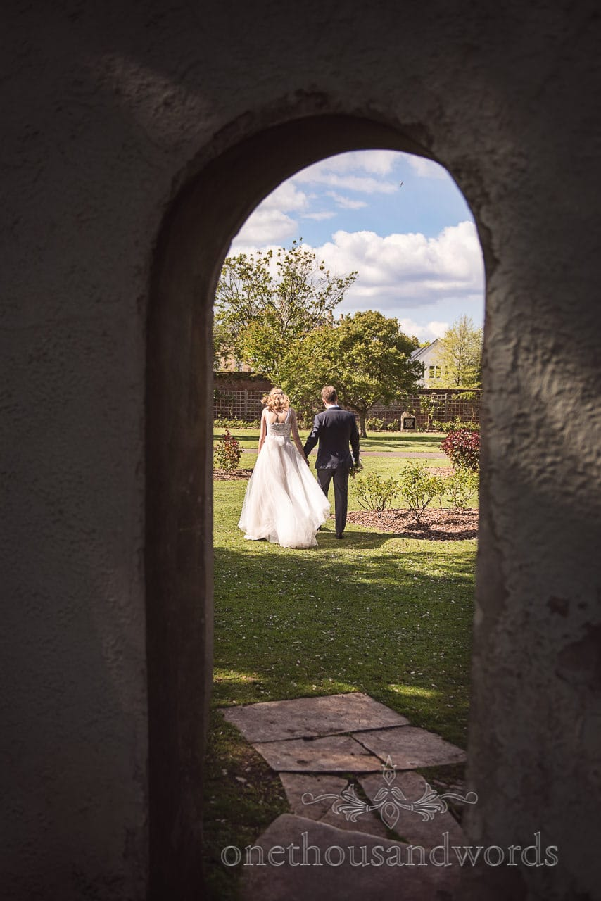 Documentary bride and Groom Wedding Photograph at Christchurch Priory Gardens Archway by one thousand words