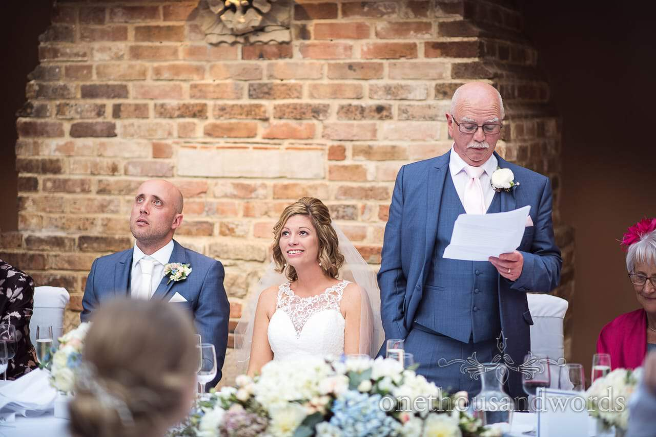 Bride and groom with worried faces as father of bride makes wedding speech