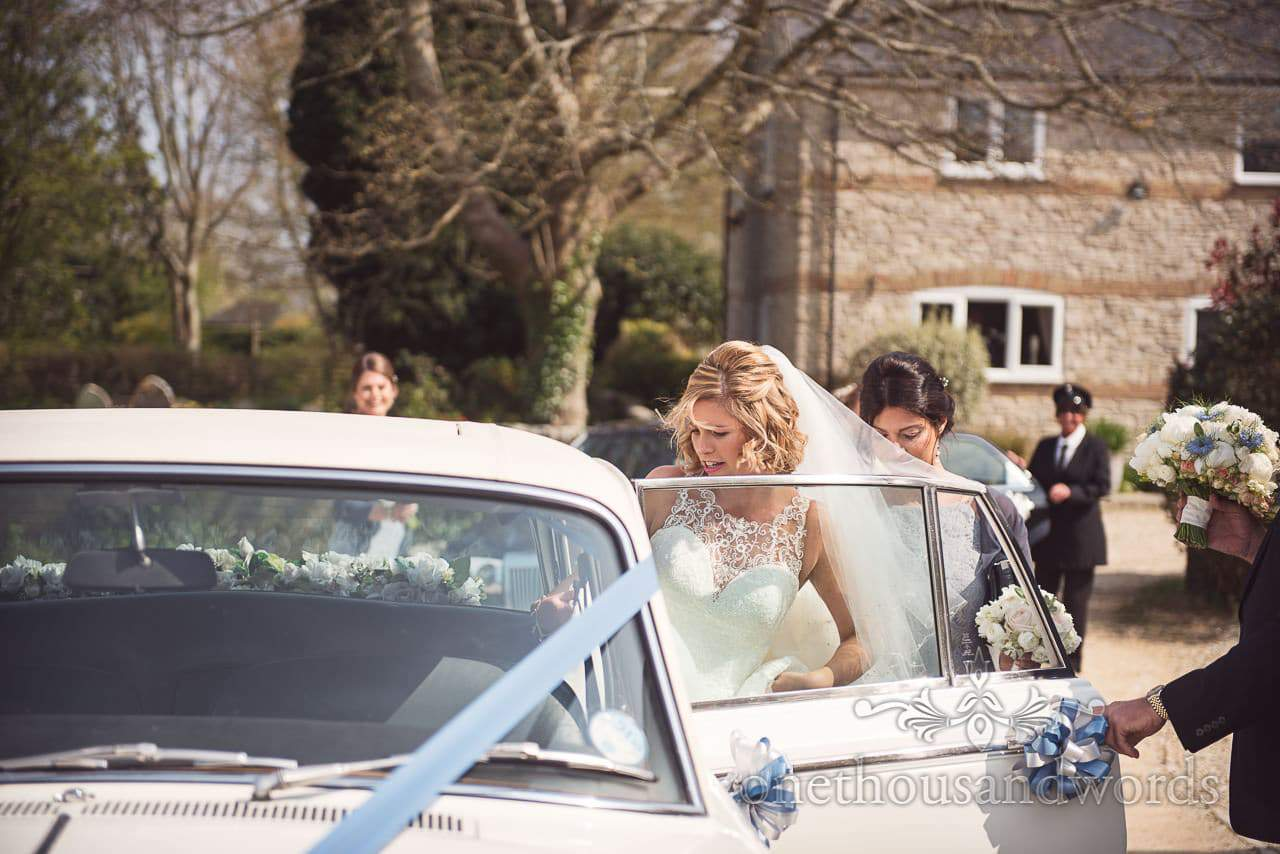 Bride is helped into classic white wedding car with blue ribbons