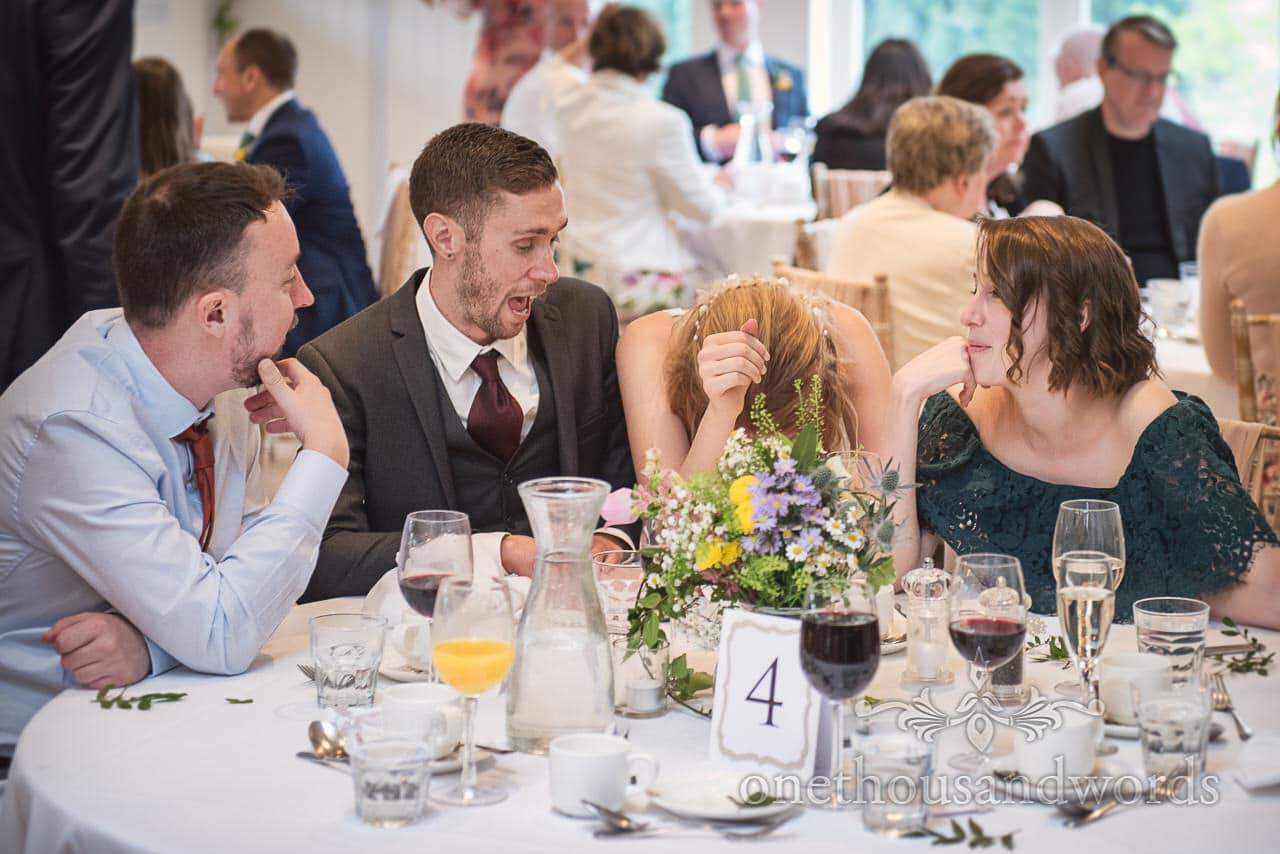 Laughing Bride Holds Head During Wedding Breakfast Jokes With Friends at Kings Arms Wedding Breakfast Table Photograph