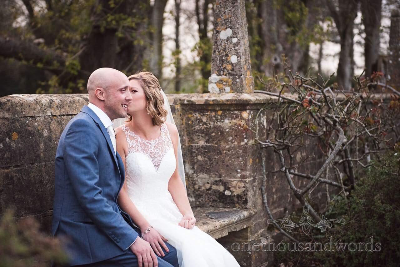Bride kisses groom in gardens at Athelhampton House Wedding venue