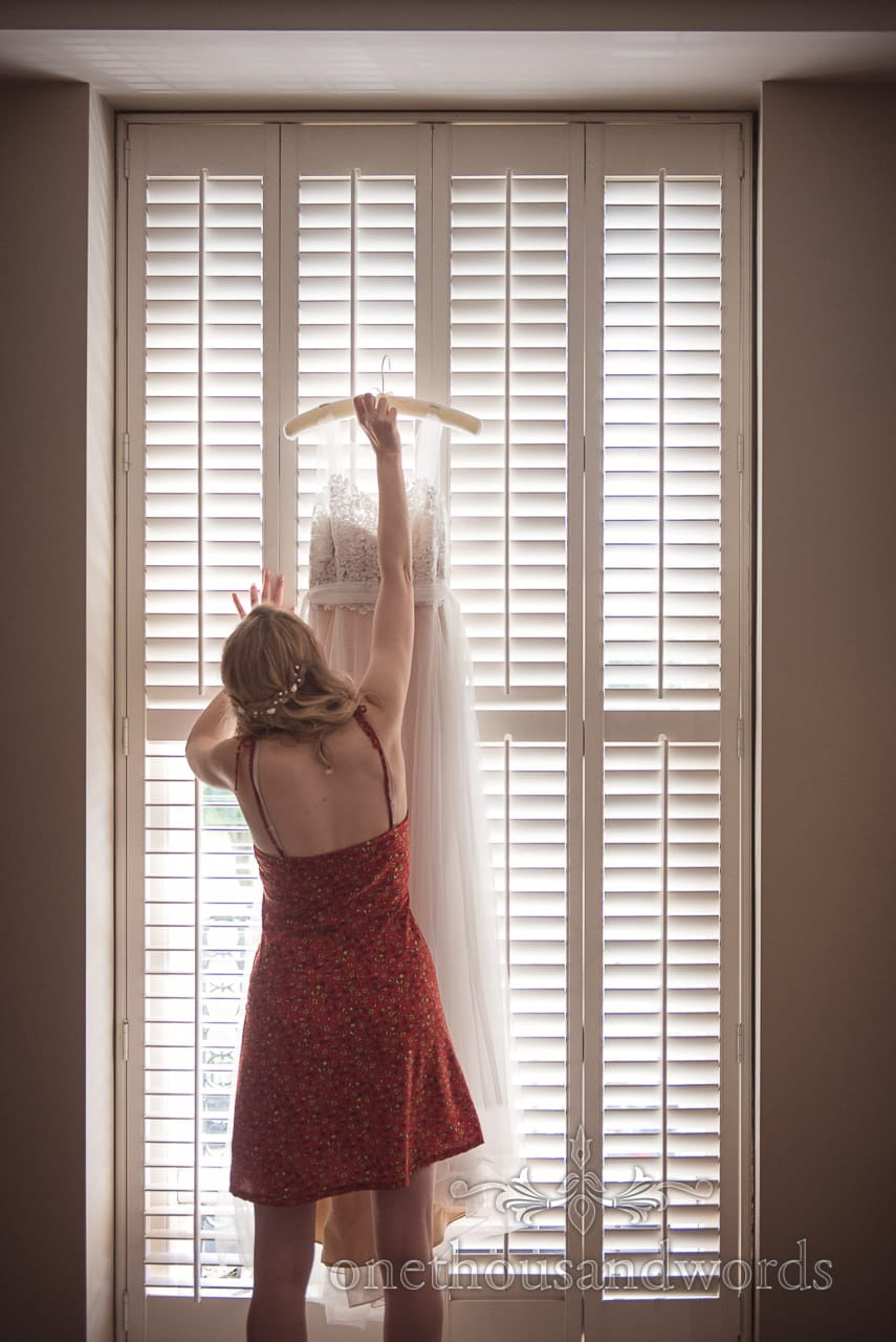 Documentary wedding photograph Bride Reaching for Wedding Dress in slatted wooden Window on Bridal Morning