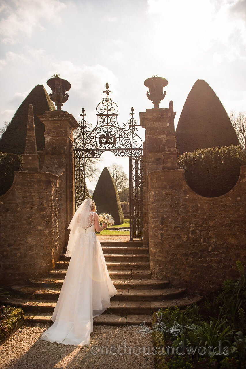 Bride walks into gardens at Athelhampton House wedding venue