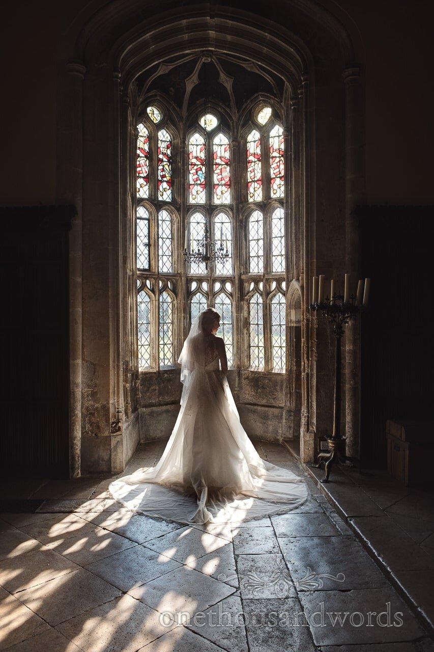 Bride in wedding dress at Oriel window at Athelhampton House Wedding