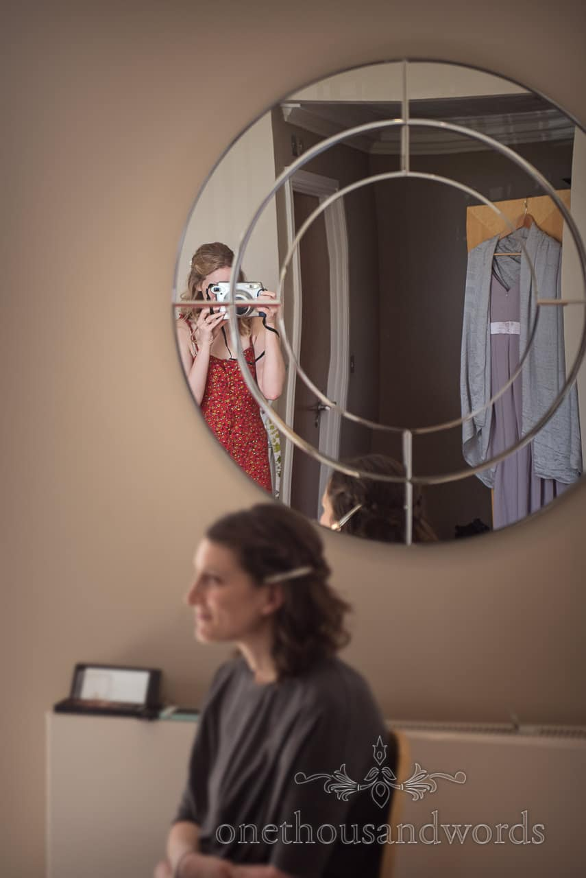 Bride takes photograph of bridesmaid on Wedding Morning With Polaroid Camera in Mirror