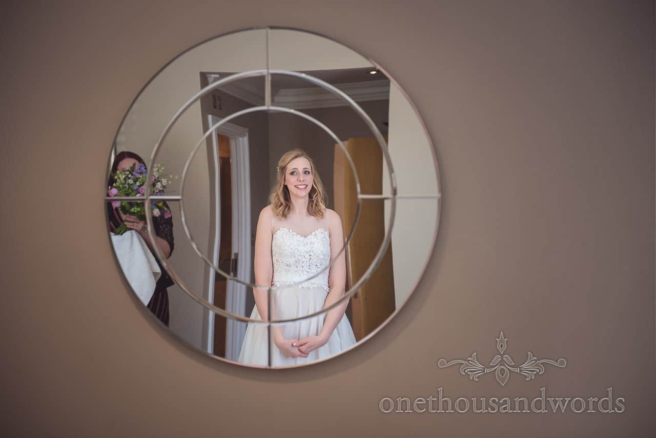 Bride in white White Wedding Dress Smiles in Reflection of Circular Target Mirror on wedding morning at Kings Arms Hotel, Christchurch