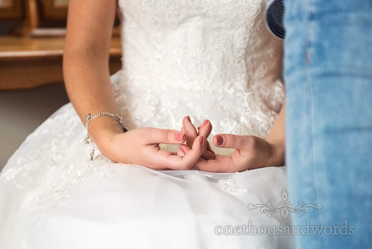 Brides hands resting on wedding dress with natural nail polish