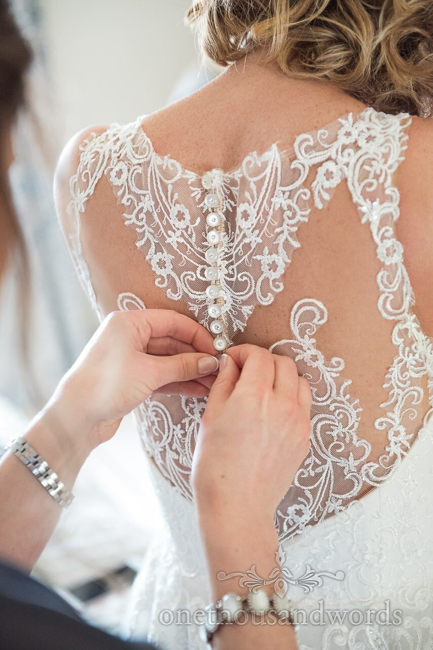 Bridesmaid buttons up wedding dress with lace detail on back