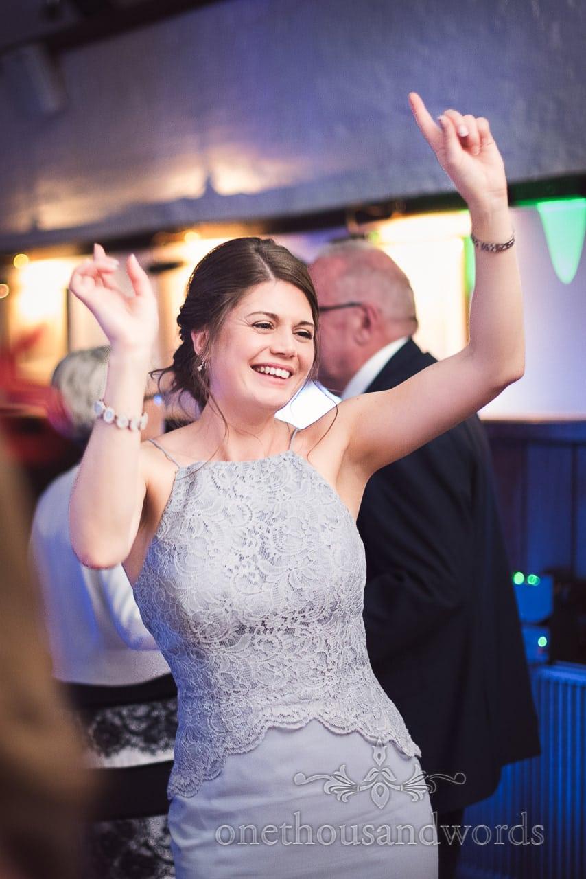 Bridesmaid in light blue detailed bridesmaids dress dancing at disco