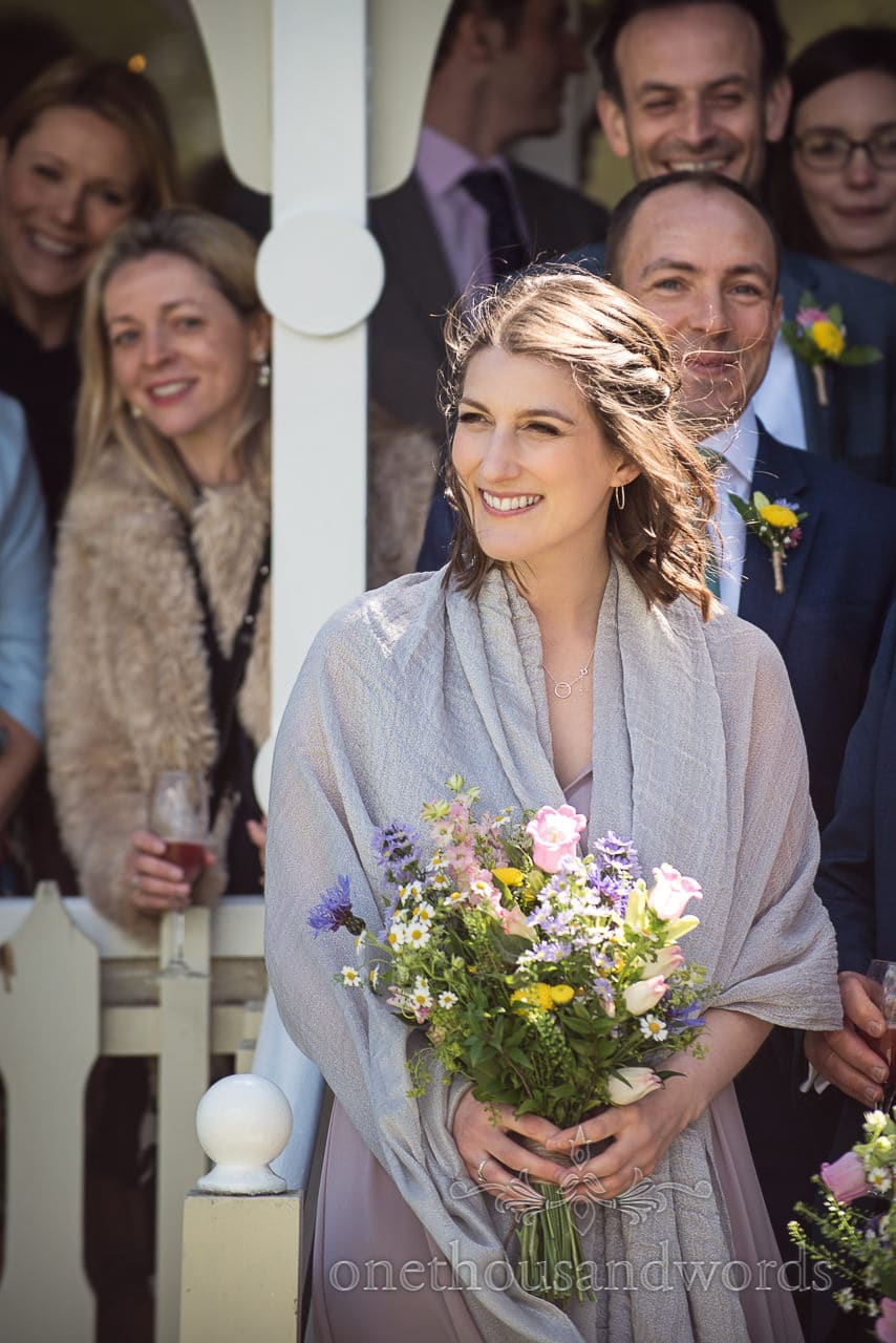 Bridesmaid Portrait Photograph With Spring Flower Wedding Bouquet During Group Photographs at Kings Arms Priory