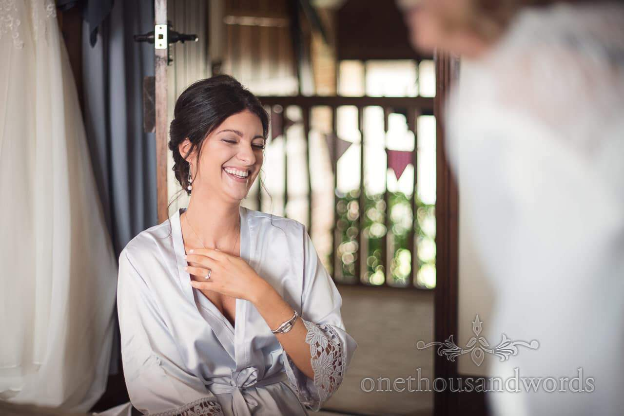 Bridesmaid in silk dressing gown laughing during bridal wedding preparations
