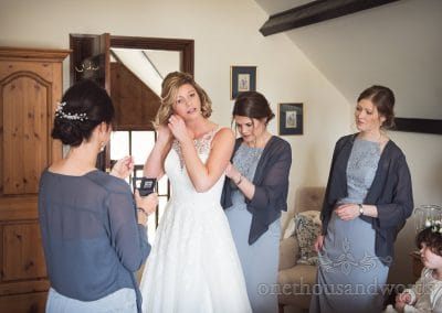 Bridesmaids in light blue dresses help bride into her wedding dress on wedding morning