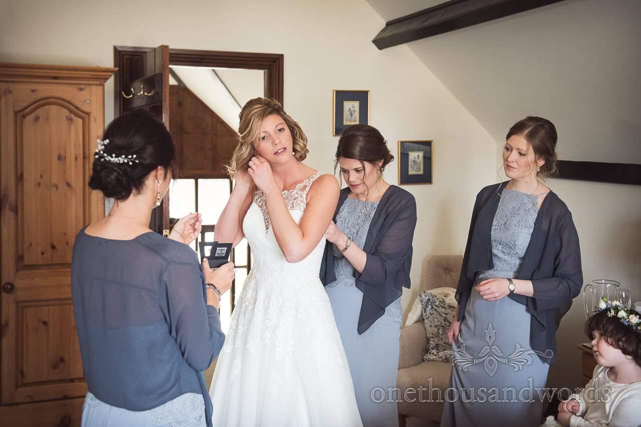 Bridesmaids in light blue dresses help bride into her wedding dress on wedding morning