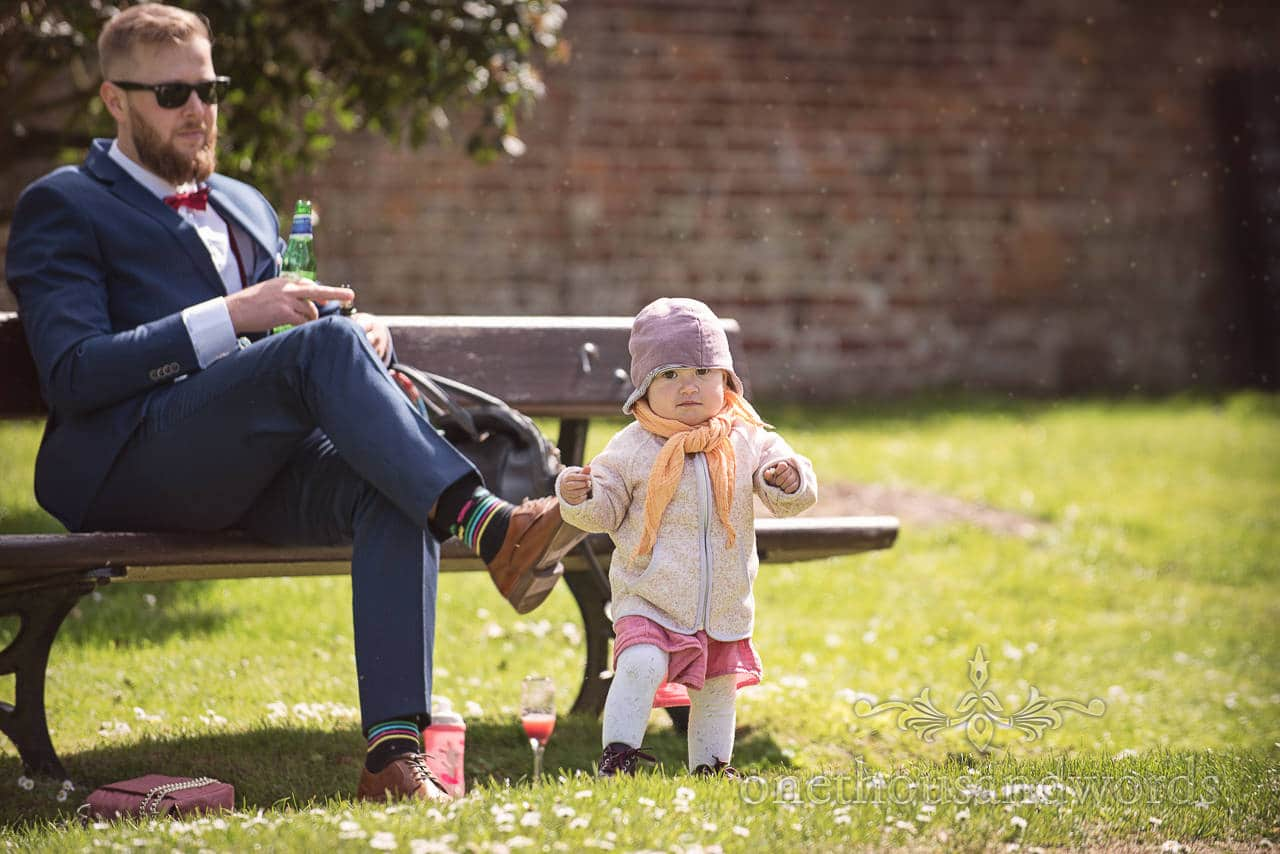 Child Wedding Guest Toddler watched by relaxing father at Kings Arms Wedding Drinks Reception in Park