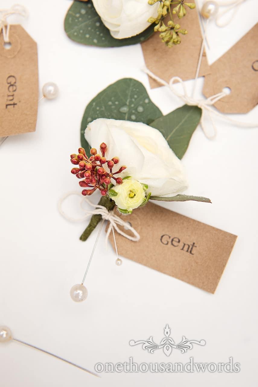 Detail wedding photograph of white wedding button hole flower