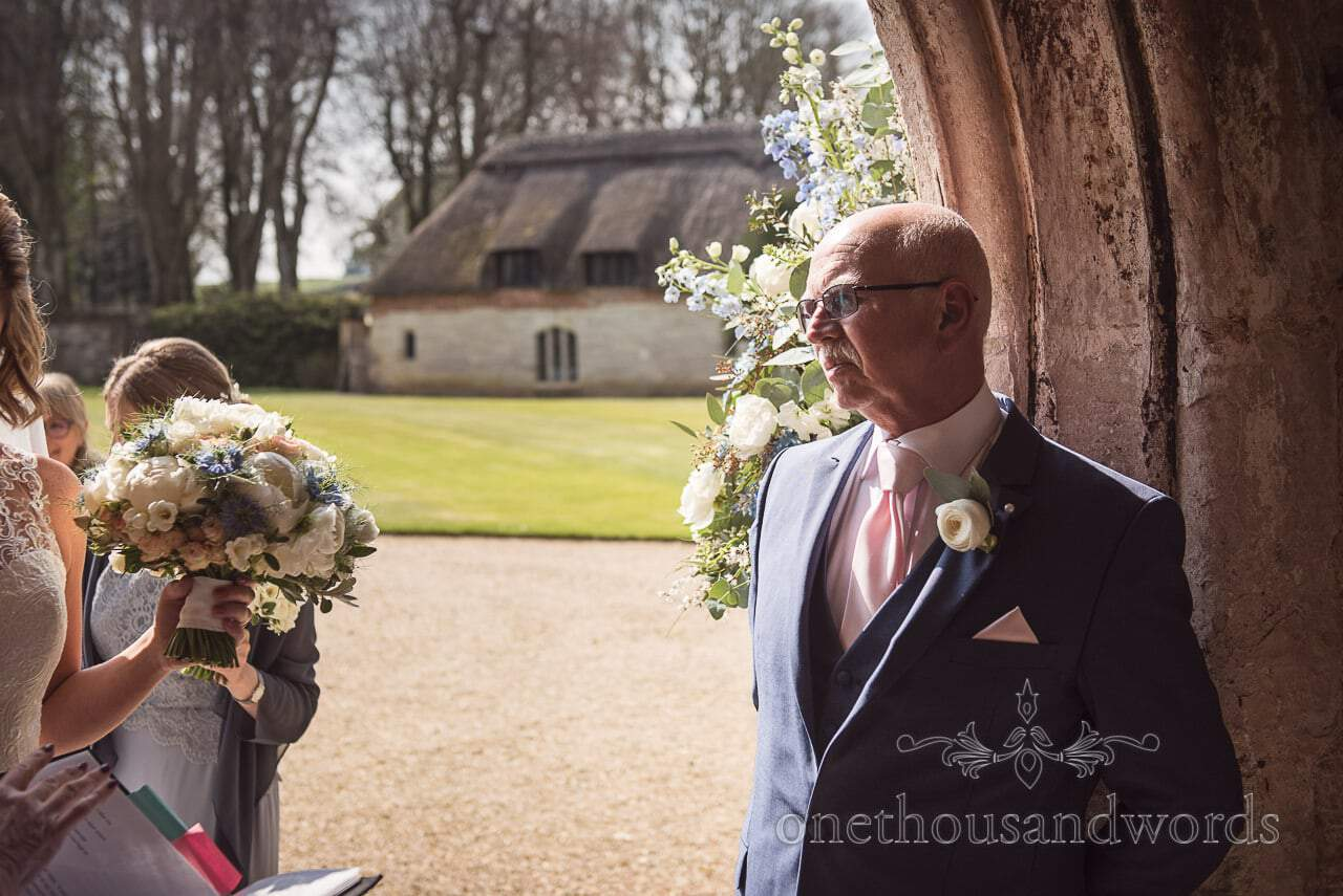 Father of bride looks at his daughter as he prepares to walk her down the aisle