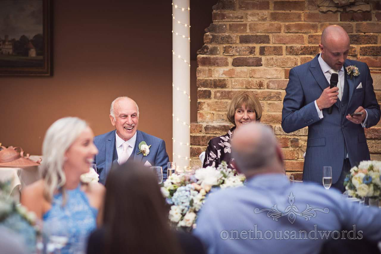 Father of the groom in blue suit laughs at grooms wedding speech