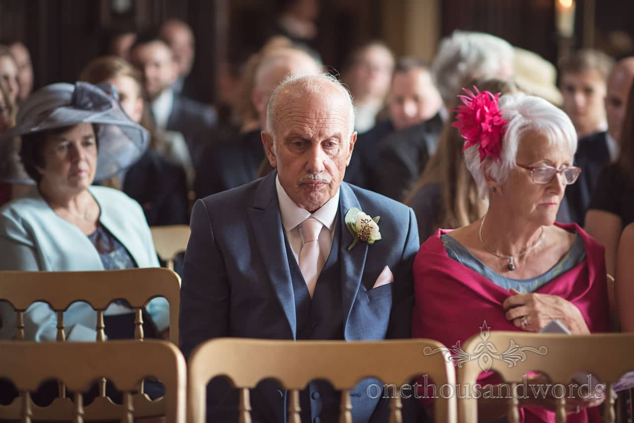 Father of the groom in blue suit waits patiently for wedding ceremony