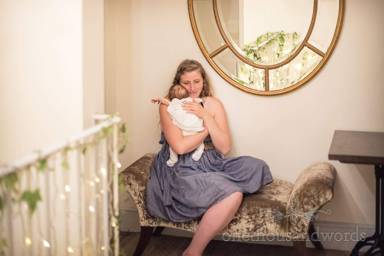 Female Wedding Guest Caring for Baby at Wedding Evening Reception Documentary Photograph by one thousand words