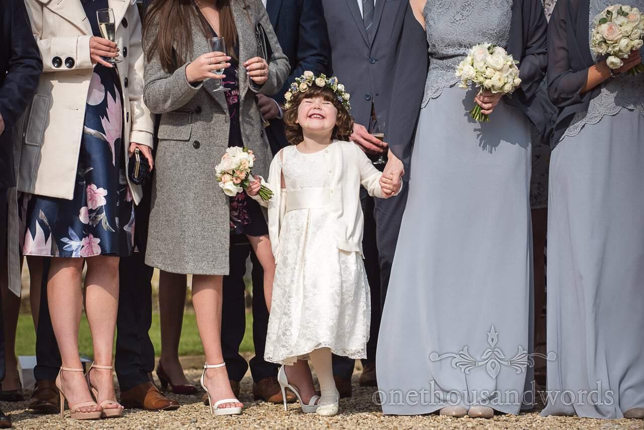 Flower girl beaming smile during wedding group photographs