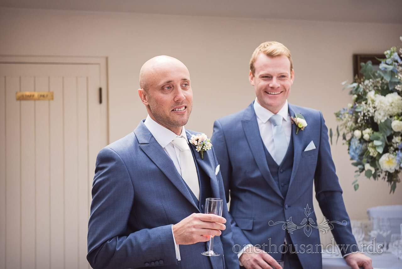 Groom and best man in blue wedding suits enjoy pre ceremony drinks