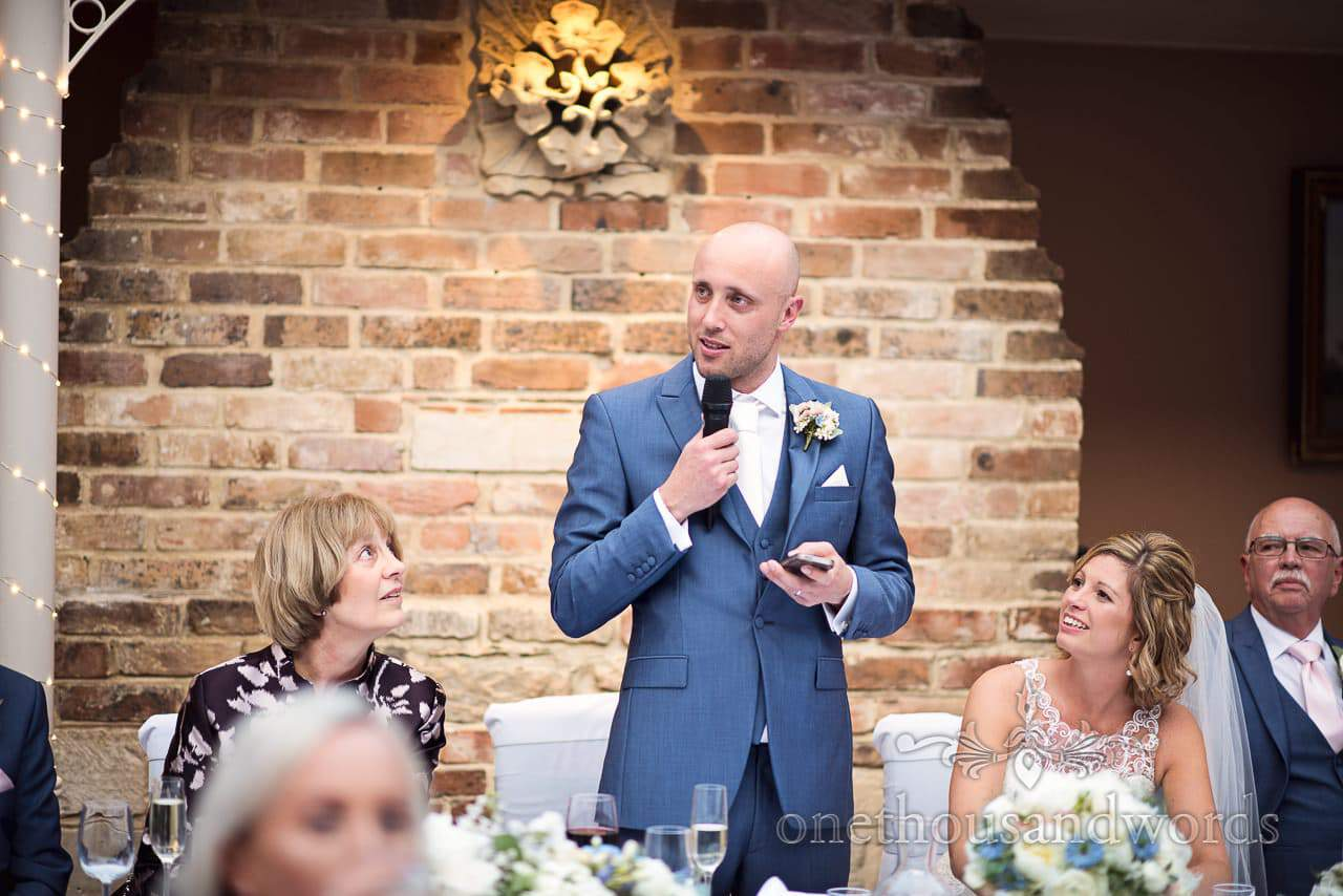 Groom in blue suit reads speech from phone at Athelhampton House Wedding photos