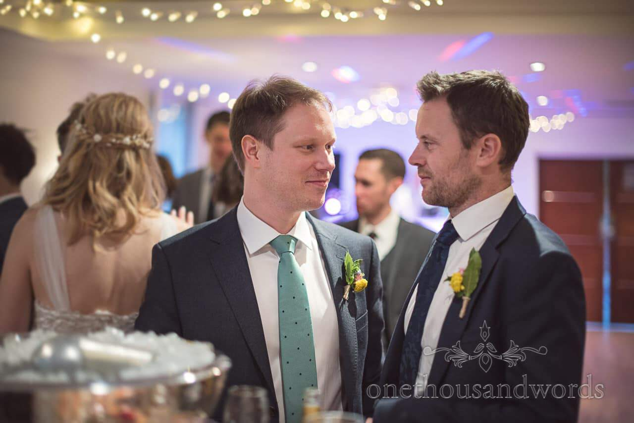 Groom and Friend Wedding Guest Share Moment at the Bar on Wedding Evening