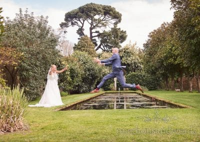 Groom jumps over ornamental pond at Athelhampton House Wedding