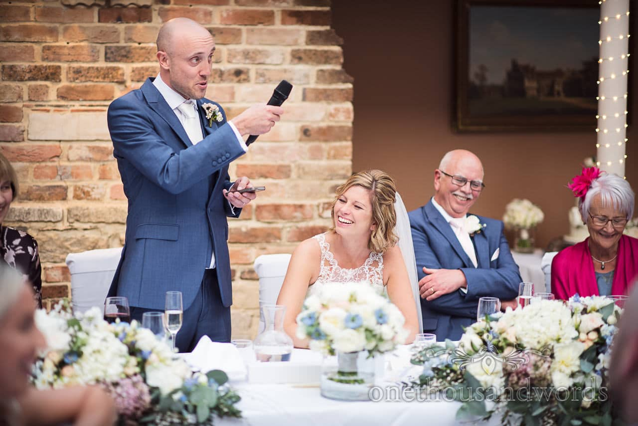 Groom uses mobile phone and microphone to make wedding speech as bride laughs