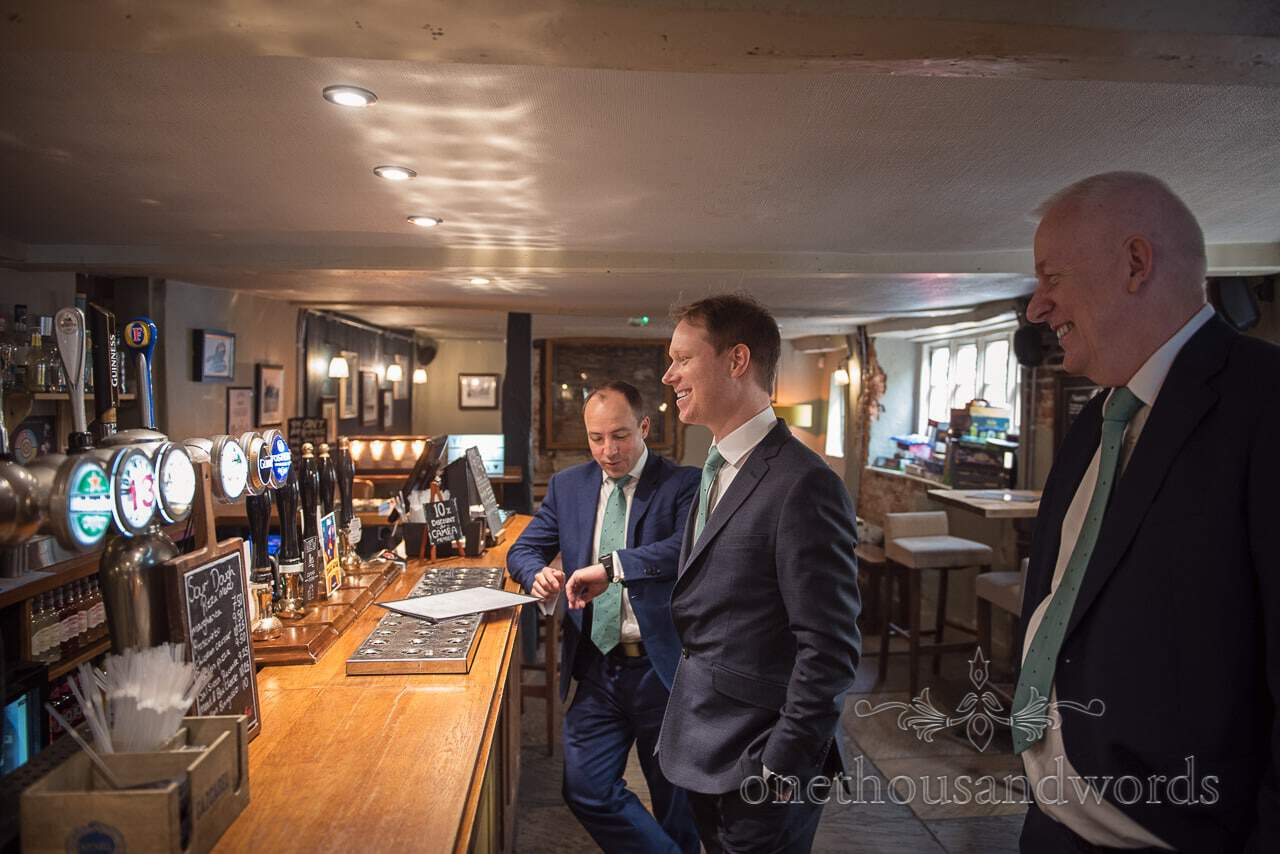 Documentary wedding photograph of Grooms Party Ordering Beer in Pub on Wedding Morning in Christchurch Dorset