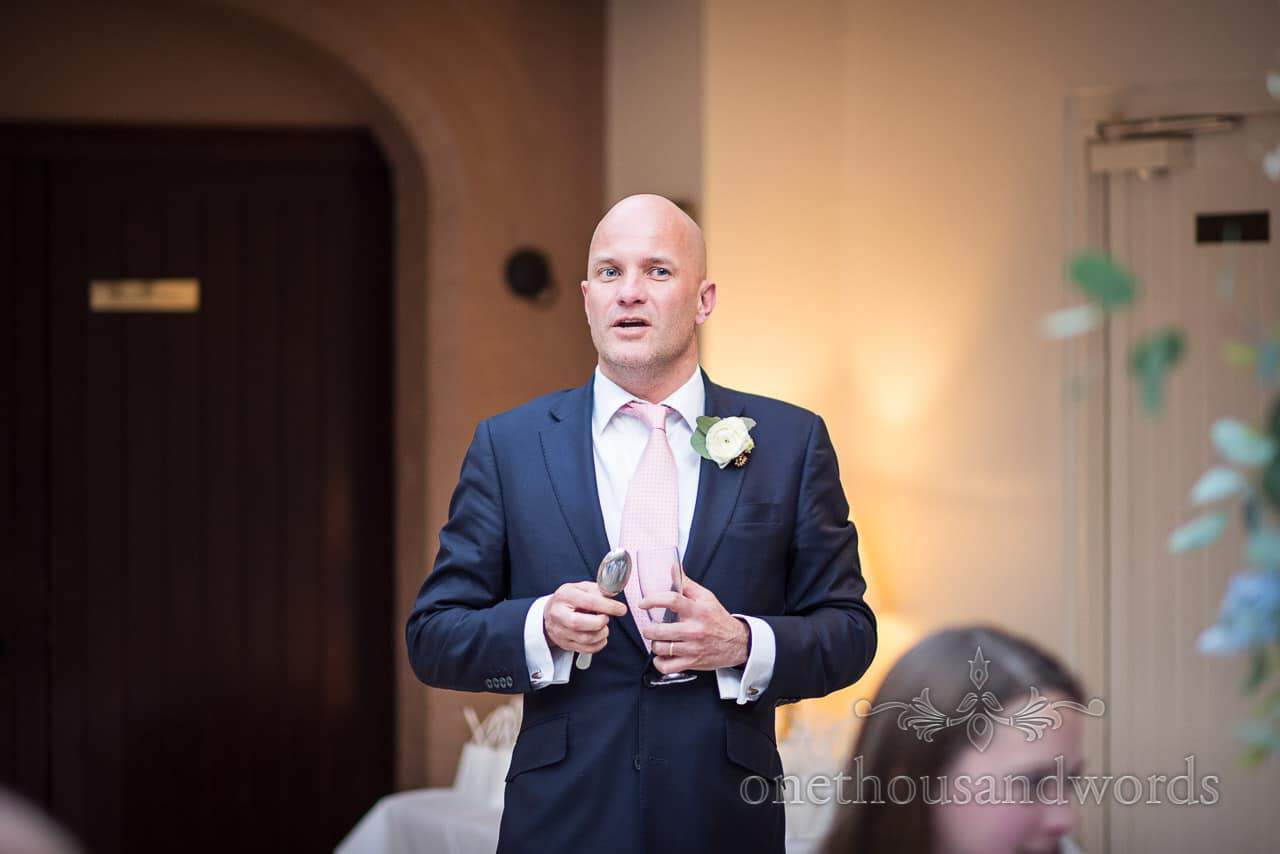 Groomsman in blue suit acts as master of ceremonies for wedding speeches