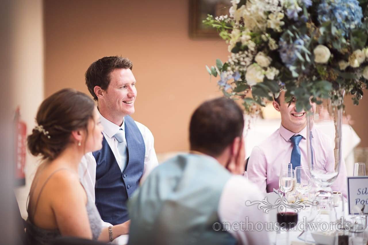 Groomsman in blue waistcoat laughing at Athelhampton House wedding breakfast