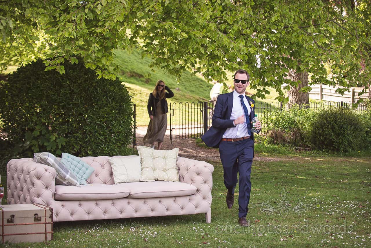 Groomsman in Blue Wedding Suit Runs past outdoor sofa at Drinks Reception at Kings Arms Wedding in Christchurch