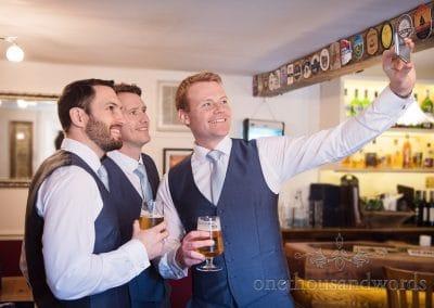 Groomsmen in blue waistcoats take selfie in pub on wedding morning
