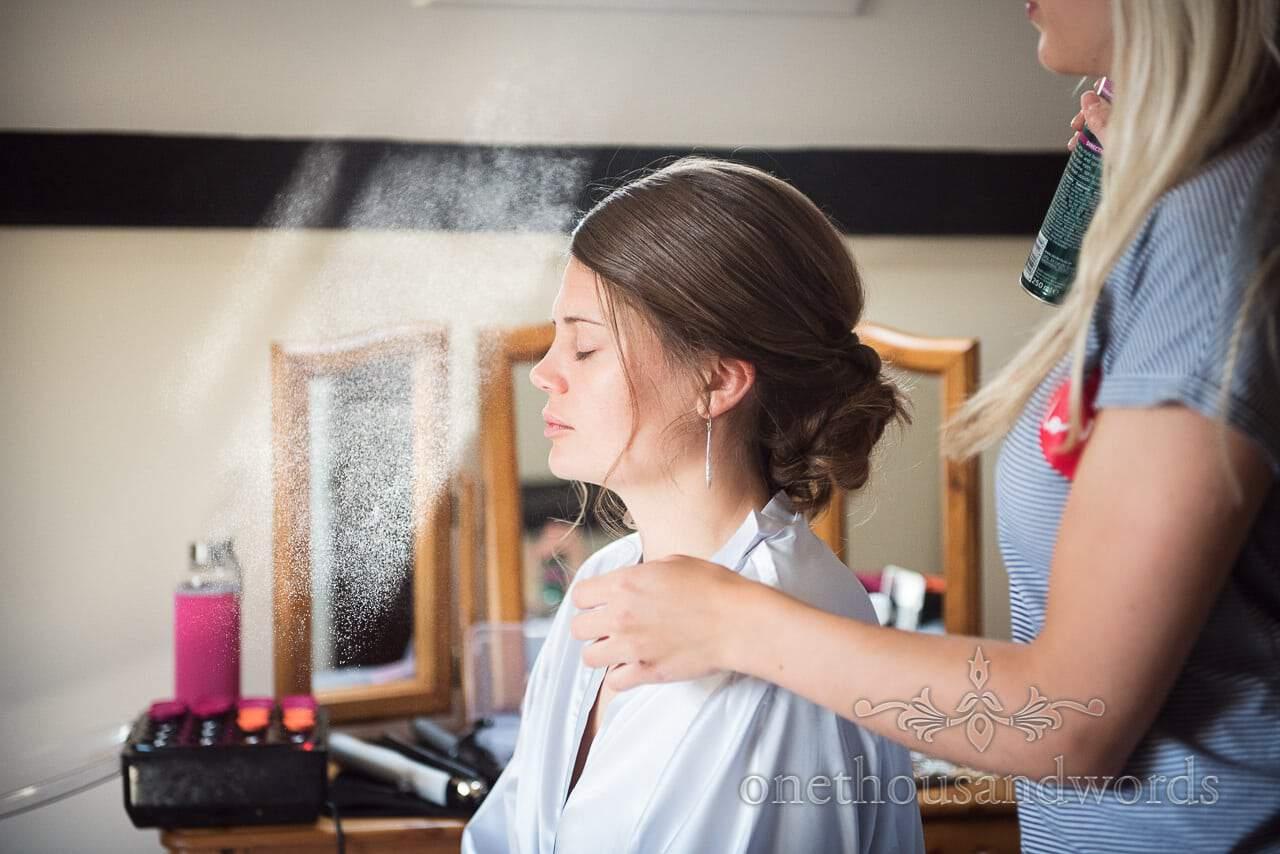 Hairspray hangs in a sun ray during bridal wedding morning preparations