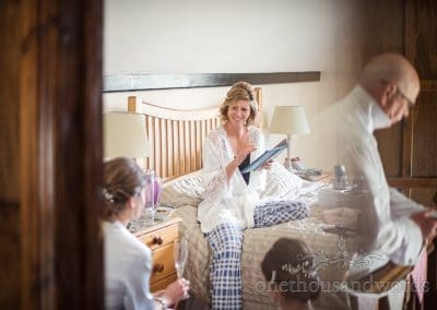 Happy bride sits on bed on wedding morning as her father also prepares