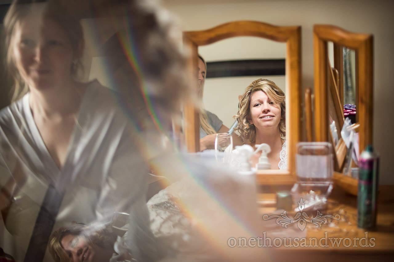 Happy bride has wedding hair styled in mirror watched by bridesmaid