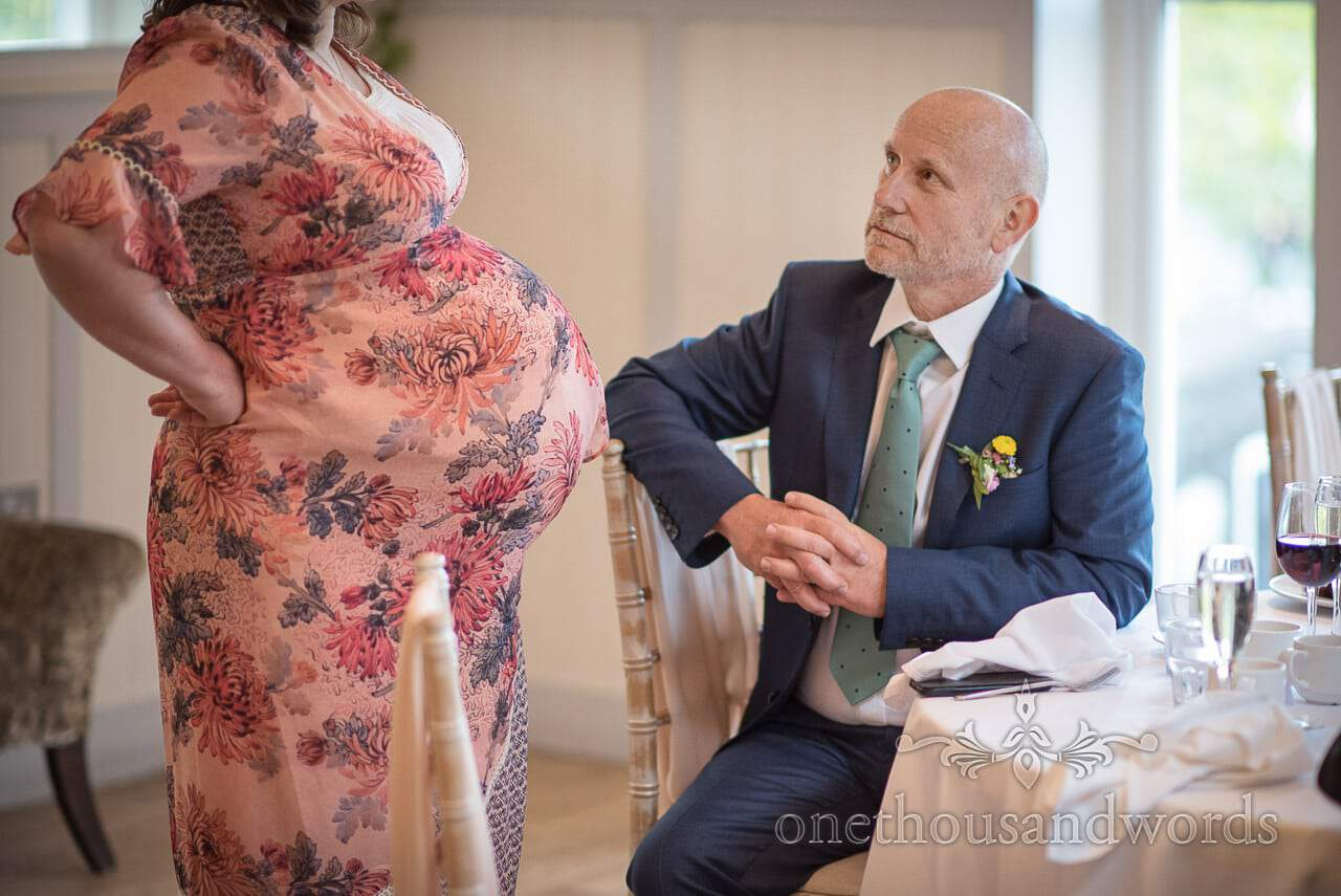 Documentary Wedding Photograph if Huge Pregnancy Bump in floral dress with Father Of Groom in blue suit Photograph