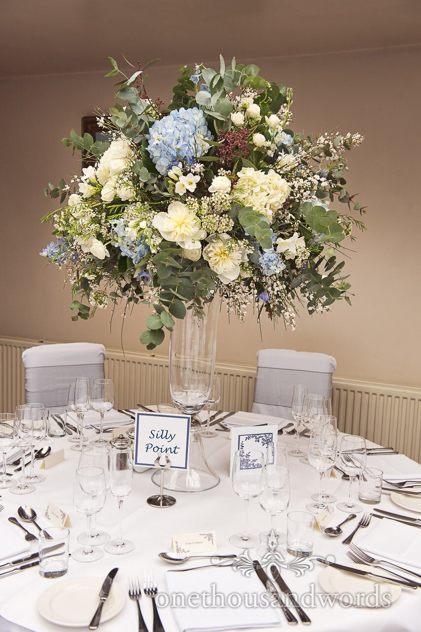 Huge wedding flower spray and wedding breakfast table at Athelhampton