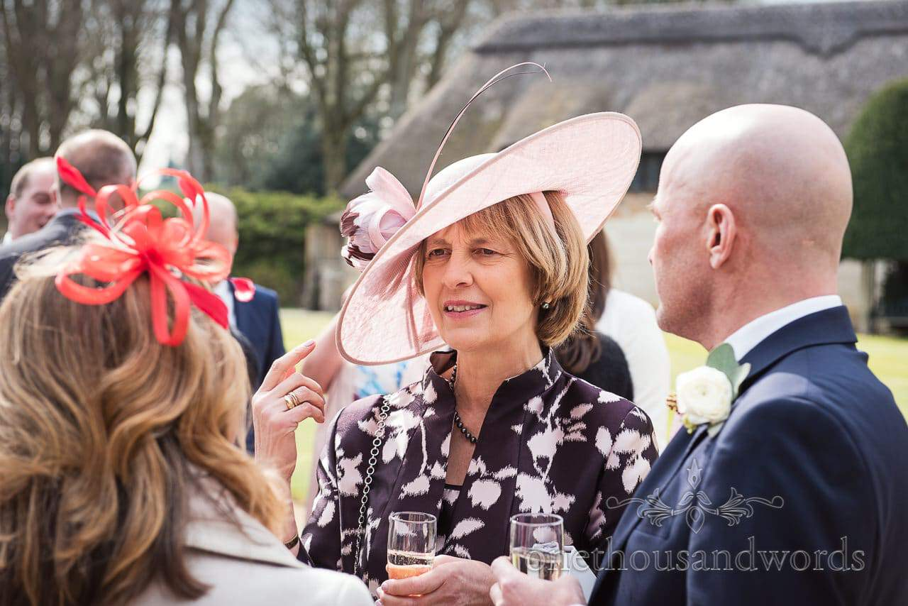 Mother of the bride in pink wedding hat at wedding drinks reception