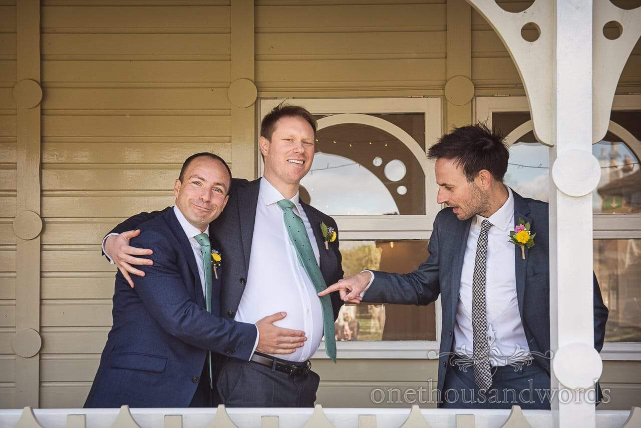 Pregnant Groom's Belly Is Poked By Joking Groomsmen Documentary Wedding Photograph at Kings Arms Pavilion Wedding