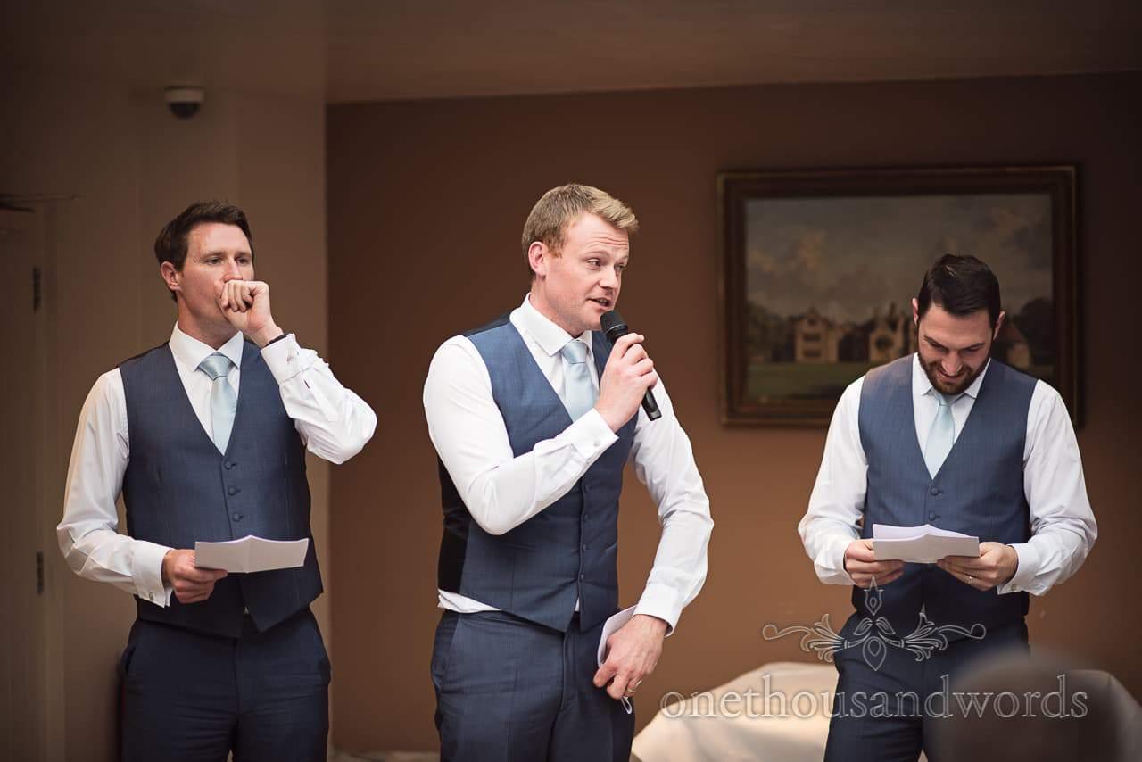 Three best men in blue waistcoats read wedding speech at Athelhampton House